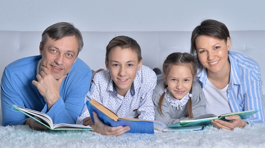 Family all reading books together.  Mom, Dad, Son and Daughter each holding a book.